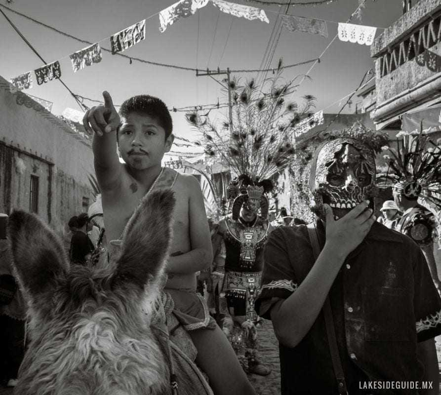 A boy dressed as San Sebastián rides on a donkey during the procession.