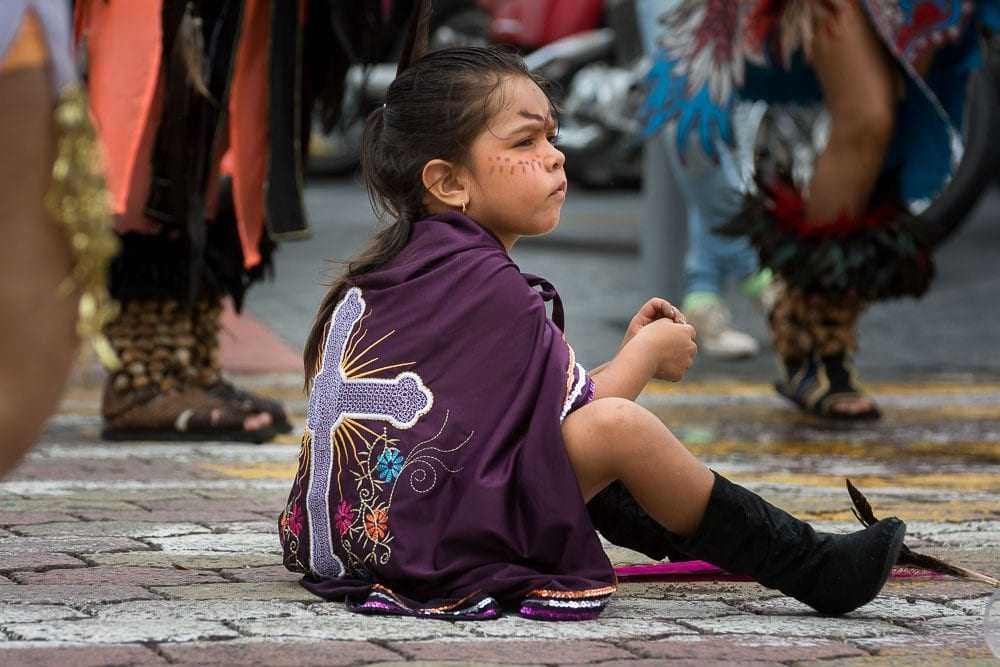 A child keeps busy while her parents dance for an hour or more after the procession ends.