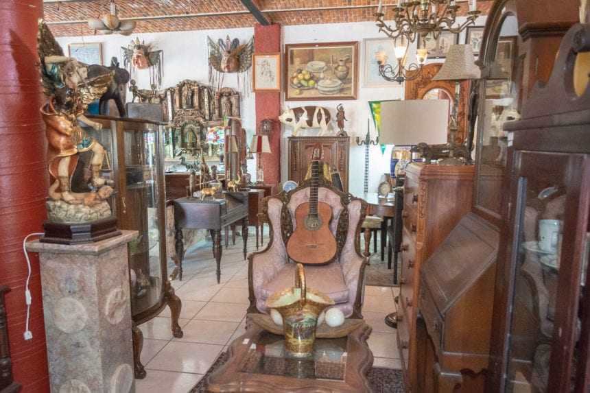 Nylong-stringed guitar, tables, dressers, dish cupboards, lamps, St. Michael statue, paintings.